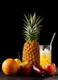 静物画热带水果和杯汁液 免版税库存图片