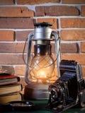 静物画煤油灯在木桌面石砖背景书照相机发光 免版税库存图片