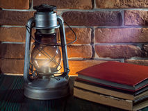 静物画煤油灯在木桌面石砖背景书照相机发光 图库摄影