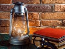 静物画煤油灯在木桌面石砖背景书照相机发光 库存图片