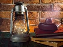 静物画煤油灯在木桌面石砖背景书照相机发光 免版税库存照片