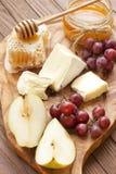 静物画用乳酪、葡萄和蜂蜜 免版税库存图片