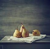 静物画用在亚麻布的秋天梨 库存照片