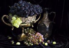 静物画用在花瓶和酒瓶的葡萄 免版税图库摄影