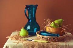 静物画用梨和蓝色水罐 免版税库存照片