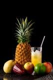静物画用热带水果和杯在黑r的汁液 免版税库存图片