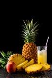 静物画用热带水果和杯在黑r的汁液 库存照片
