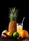 静物画用热带水果和杯在黑r的汁液 免版税库存照片