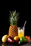 静物画用热带水果和杯在黑r的汁液 图库摄影