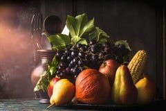 静物画用秋天水果和蔬菜:苹果,梨,葡萄,南瓜,在黑暗的土气厨房用桌上的玉米棒子 图库摄影