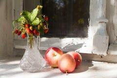 静物画用红色苹果和草莓在花瓶 老窗口基石,村庄房子背景 夏天,晴天 库存图片