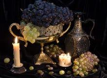 静物画用葡萄在花瓶和蜡烛 免版税库存照片
