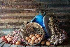 静物画用鸡蛋、葱、大蒜、胡椒和老蓝色标度 库存图片