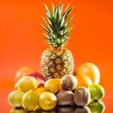 静物画菠萝和各种各样的果子在橙色背景,方形的射击 免版税图库摄影
