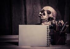 静物画颜色铅笔写生簿和头骨在木背景 免版税库存照片
