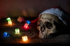 静物画头骨穿戴有礼物火焰信号器的圣诞老人帽子 库存照片