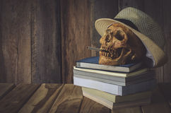 静物画头骨 盖帽机器织法和书在木背景 库存图片