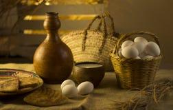 静物画鸡蛋和牛奶在篮子 免版税库存照片