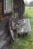 静物画:倾斜在小屋的墙壁的老木轮子 库存照片