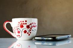 静物画Coffe杯子和电话 免版税图库摄影