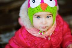 非常一个红色夹克和帽子的逗人喜爱的女孩有猫头鹰的 免版税库存照片