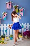 非常一条蓝色裙子的逗人喜爱的长发女孩有小鸡的为 图库摄影