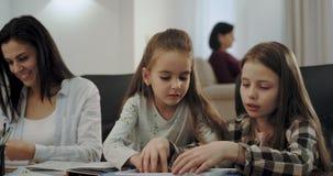 非常一起使用在台式游戏机的逗人喜爱的两姐妹,当他们的母亲是背景阅读的a时繁忙和老婆婆 影视素材