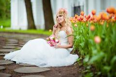 非常一件白色礼服的美丽的新娘金发碧眼的女人有一个异常的猪圈的 库存图片