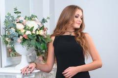 非常一件黑礼服的可爱的少妇在镜子附近和 图库摄影