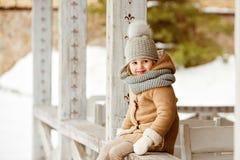 非常一件米黄外套和一个灰色帽子的si好美丽的女孩孩子 免版税图库摄影