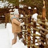 非常一件米黄外套和灰色帽子st的好美丽的女孩孩子 免版税库存图片