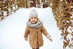 非常一件米黄外套的好美丽的女孩孩子和一个灰色帽子去 免版税库存图片
