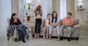 非常使用与他们的在一个电子游戏的孩子的被集中的和吸引人母亲在照相机前面坐 股票录像