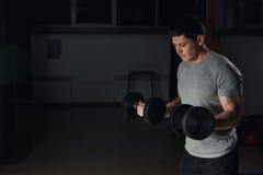 非常供给运动人爱好健美者动力,执行与哑铃的锻炼,在黑暗的健身房 免版税图库摄影