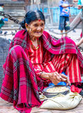 非常卖五谷的老尼泊尔妇女为鸽子在寺庙 库存图片