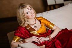 非常印度红莎丽服说谎的美丽和肉欲的白肤金发的女孩 库存图片