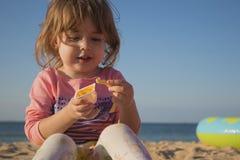 非常吃炸薯条和调味汁的俏丽的女孩 女孩坐在海滩的沙子反对海 库存照片