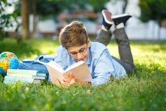 非常圆的玻璃的逗人喜爱,年轻男孩和蓝色衬衣在草读说谎在背包和地球旁边的书 教育 库存图片
