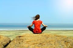 非常在山峰的年轻健身妇女实践瑜伽 免版税库存图片