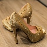 非常在金子的原始的被停顿的鞋子与钉子的装饰在镶花地板上的 免版税库存照片