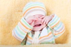 非常坐在一张温暖的羊皮的疲乏的困婴孩 免版税图库摄影