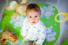非常坐在幼儿围栏的睡衣的逗人喜爱的女孩 图库摄影