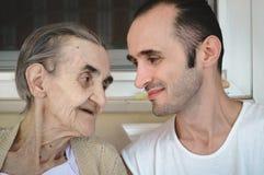 非常坐在有她的孙子的阳台上的老资深妇女 库存图片