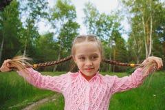非常嬉戏的小女孩开玩笑地伸出了她的舌头 免版税库存照片