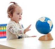 非常小,但是严肃的小女孩转动的地球 库存照片