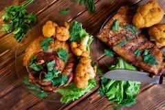 非常开胃油煎的猪肉指关节和肋骨、荷兰芹、莴苣、花椰菜和莳萝在透明板材在一把快刀旁边 图库摄影