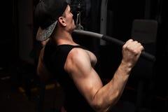 非常强有力的运动人爱好健美者、锻炼后面的和手 健身房的一个人 库存照片