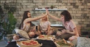 非常微笑和吸引人在PSP的夫人多种族戏剧在照相机前面在吃比萨的现代卧室 影视素材