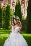 非常性感和热的白肤金发的式样女孩,白色礼服和花卉花圈的在她的头,在教会前面走 库存图片