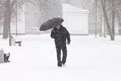 非常恶劣天气在一个城市在冬天:可怕的大雪和飞雪 男性步行掩藏从雪在伞下 免版税库存照片
